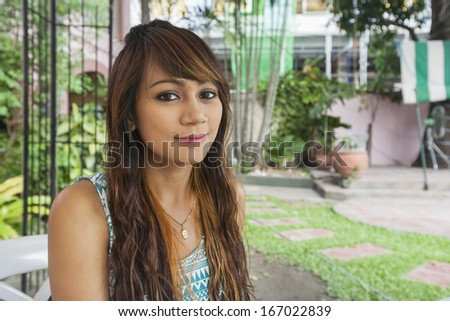 Portrait of beautiful young woman smiling outdoors; Manila; Philippines - stock photo
