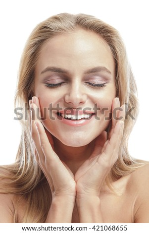 portrait of beautiful young woman smiling while touching her face with closed eyes isolated on white background