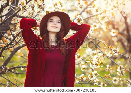 portrait of beautiful young woman standing near blooming tree - stock photo