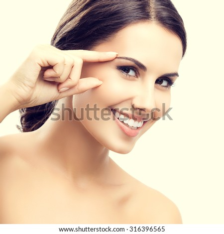 Portrait of beautiful young woman touching skin or applying cream - stock photo
