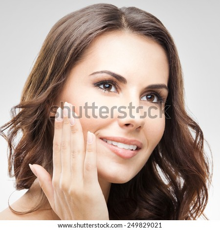 Portrait of beautiful young woman touching skin or applying cream, against grey background - stock photo