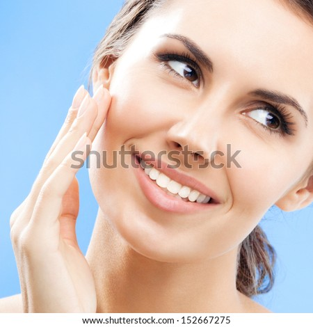 Portrait of beautiful young woman touching skin or applying cream, over blue background - stock photo