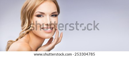 Portrait of beautiful young woman touching skin or applying cream, with blank copyspace area for text or slogan, against grey background - stock photo