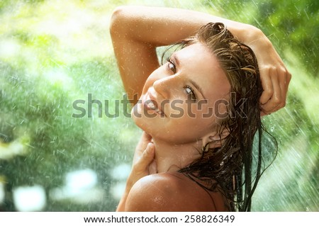 Portrait of beautiful young woman under summer rain in green park - stock photo