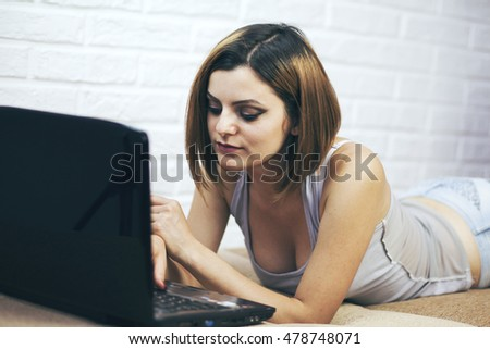 Portrait of beautiful young woman using her laptop in the bed.