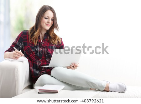 Portrait of beautiful young woman using her laptop while working from home. - stock photo
