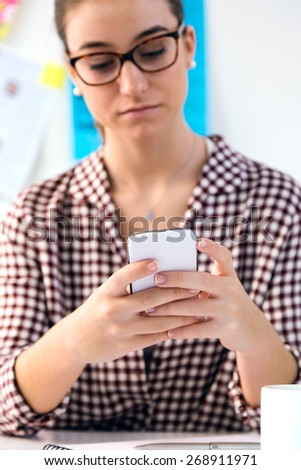 Portrait of beautiful young woman using her mobile phone in the office. - stock photo