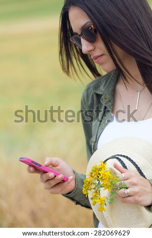 Portrait of beautiful young woman using her mobile phone in the park. - stock photo
