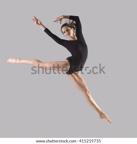 Portrait of beautiful young woman wearing black sportswear working out in studio. Fit sporty girl doing split leap in the air. Jumping, dancing. Full length. Side view. Square image - stock photo