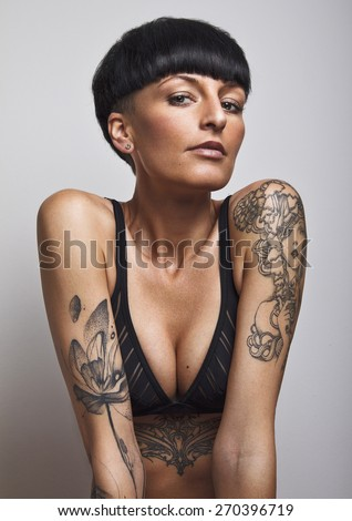 Portrait of beautiful young woman wearing black underwear. With black mushroom hair cut, lot of tattoos on her body and sexy looking at camera. Developed from RAW. Retouched with special care. - stock photo