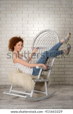 portrait of beautiful young woman wearing jeans, shirt and sneakers with red curly hair with her feet up on the wicker rocking chair against white bricks wall - stock photo