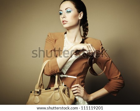 Portrait of beautiful young woman with a leather bag. Fashion photo - stock photo