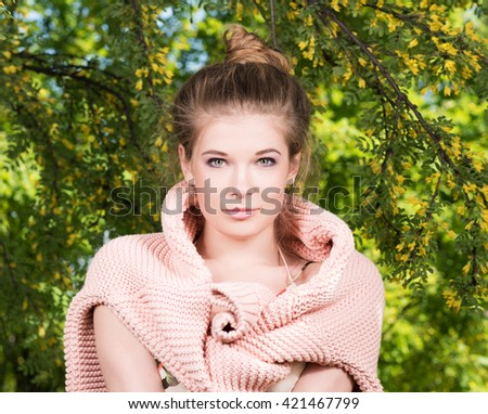 Portrait of beautiful young woman with a pink sweater on his shoulders in a lush garden. Collected hair, light makeup - stock photo