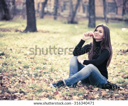 Portrait of beautiful young woman with apple in autumn park - stock photo