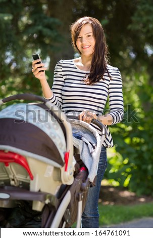 Portrait of beautiful young woman with baby carriage using cell phone in park - stock photo