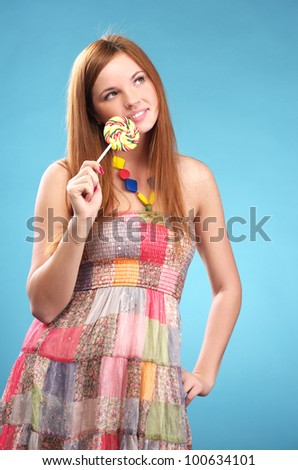 Portrait of beautiful young woman with big lollipop - stock photo