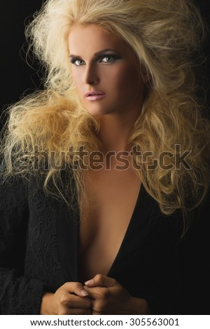 Portrait of beautiful young woman with bright makeup and fluffy blond hair