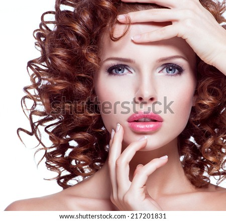 Portrait of beautiful young woman with brunette curly hair posing at studio. Closeup face with curly hairstyle, isolated on white. - stock photo