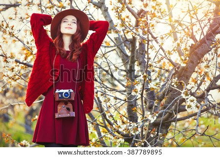 portrait of beautiful young woman with camera and hat standing near blooming tree - stock photo