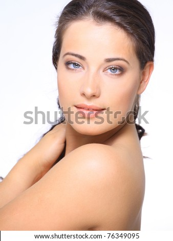 Portrait of beautiful young woman with clean skin looking at camera - stock photo