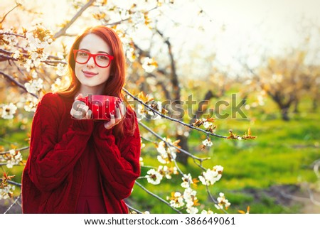 portrait of beautiful young woman with cup standing near blooming tree - stock photo