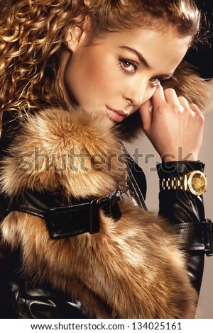 Portrait of beautiful young woman with curly hair wearing fashionable fur and gold watch, looking at camera. - stock photo