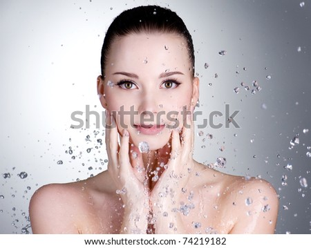 Portrait of beautiful young woman with drops of water around her face - horizontal - stock photo