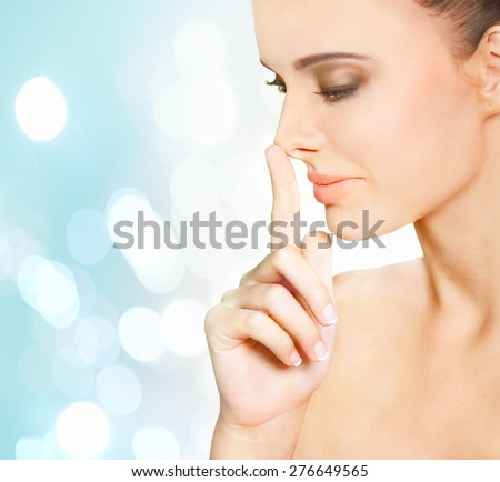 Portrait of beautiful young woman with fingertip touching her nose - stock photo