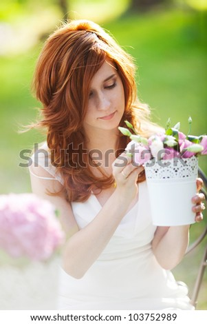 portrait of beautiful young woman with flowerpot in the hands - stock photo