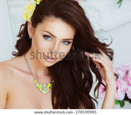 Portrait of Beautiful Young Woman with Flowers. Healthy Long Hair and Clear Skin. Close Up