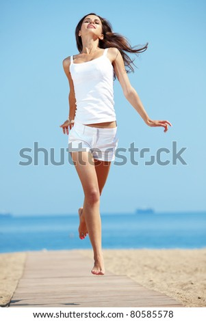Portrait of beautiful young woman with golden tan resting at beach in summer - stock photo