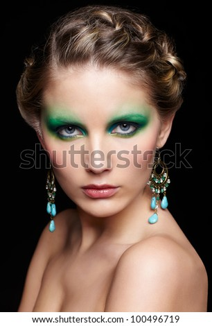 portrait of beautiful young woman with green and blue eye shade make up on black