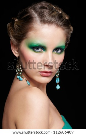 portrait of beautiful young woman with green and blue eye shade make up posing on black