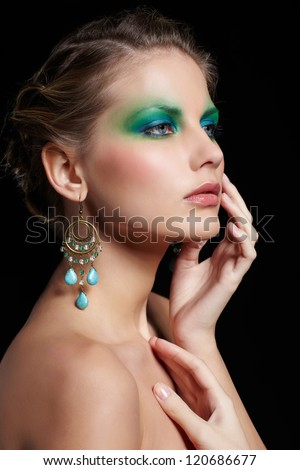 portrait of beautiful young woman with green and blue eye shade make-up touching cheek