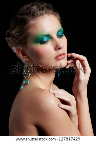 portrait of beautiful young woman with green and blue eye shade make-up touching her cheek - stock photo