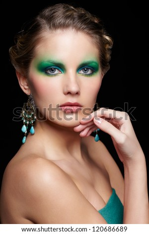 portrait of beautiful young woman with green and blue eye shade make up touching her chin