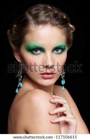 portrait of beautiful young woman with green and blue eye shade make up touching her shoulder