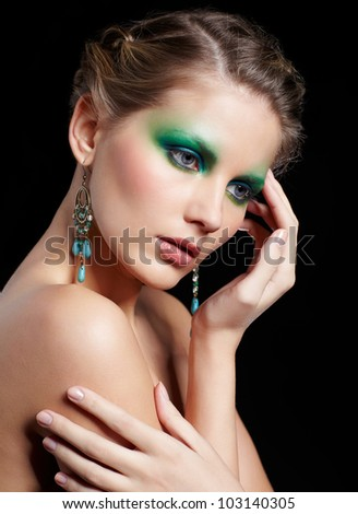 portrait of beautiful young woman with green and blue eye shade make-up touching her shoulder and temple