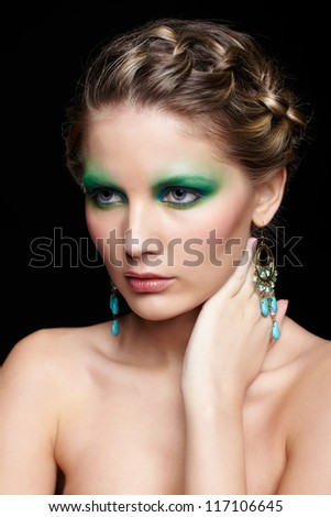 portrait of beautiful young woman with green and blue eye shade make up touching neck