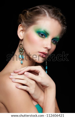 portrait of beautiful young woman with green and blue eye shade make up touching shoulder - stock photo