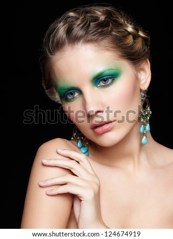 portrait of beautiful young woman with green and blue eye shade make-up touching shoulder