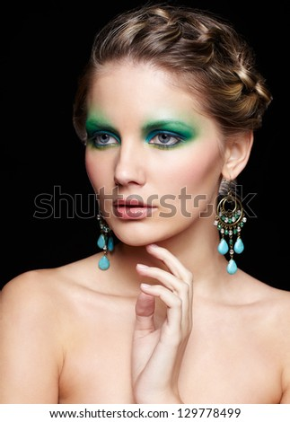 portrait of beautiful young woman with green and blue eye shade makeup touching her chin
