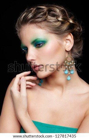 portrait of beautiful young woman with green and blue eye shade makeup touching her shoulder