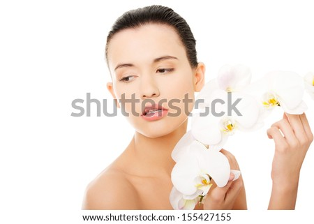 Portrait of beautiful young woman with health skin and with orchid flower. Spa concept.