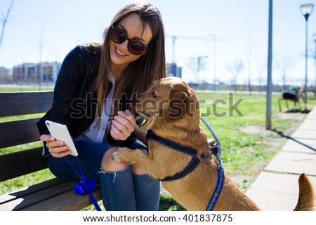 Portrait of beautiful young woman with her dog using mobile phone.