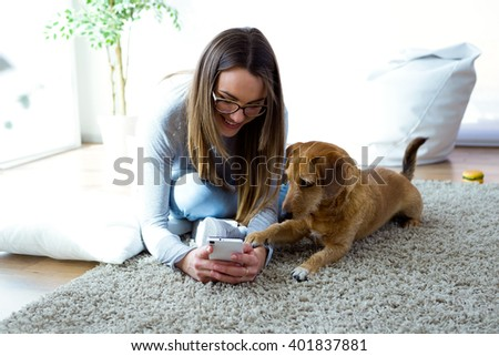 Portrait of beautiful young woman with her dog using mobile phone at home. - stock photo