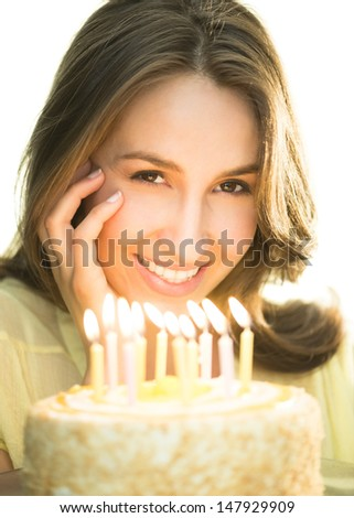 Portrait of beautiful young woman with lit candles on cake - stock photo