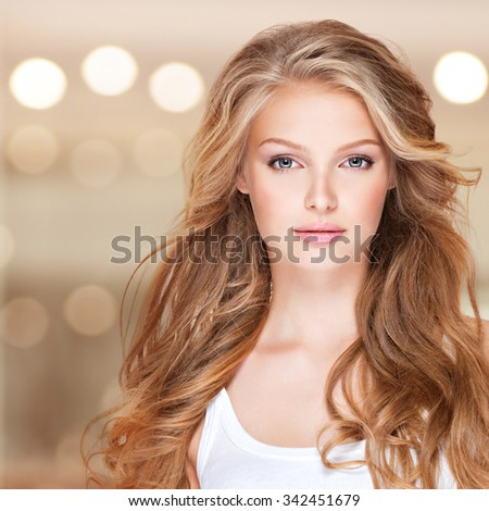 Portrait of beautiful young woman with long curly hair. Closeup face of a pretty caucasian model looking at camera - stock photo
