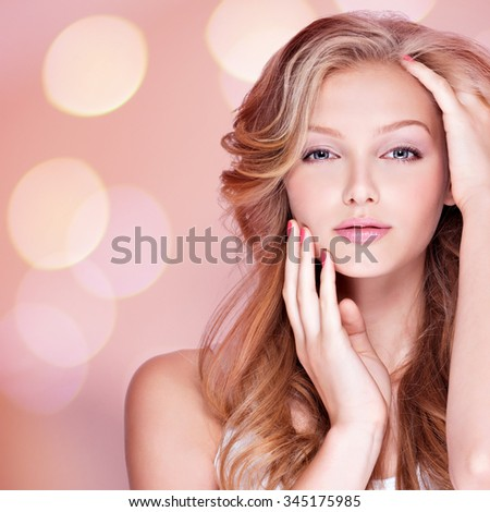 Portrait of beautiful young woman with long curly hair touching her face. Fashion model posing at studio - stock photo
