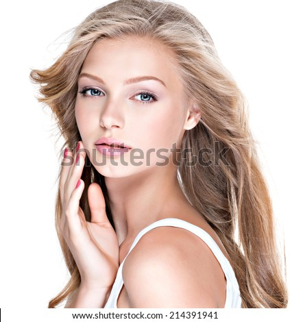 Portrait of beautiful young woman with long curly hair touching her face - isolated on white. - stock photo